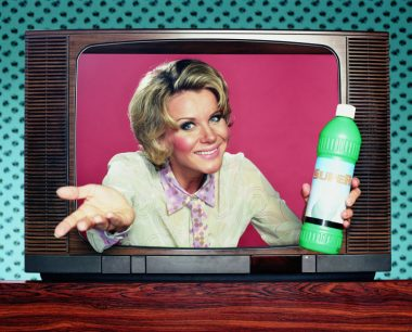 Woman holding domestic product emerging from television, portrait
